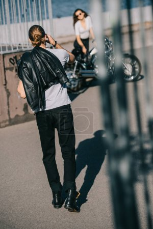 selective focus of biker going to girlfriend with classical chopper motorbike