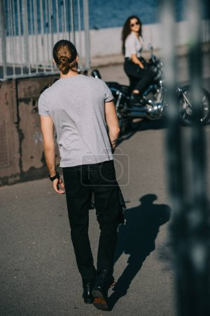 selective focus of man going to girlfriend with cruiser motorbike
