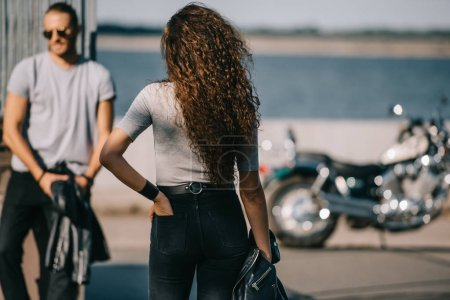 Photo for Back view of woman going to man with classical motorbike - Royalty Free Image