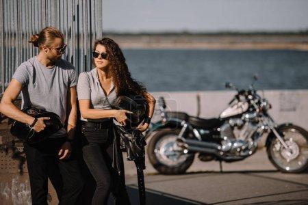 Photo pour Couple de jeunes motards portant des casques, moto classique sur fond - image libre de droit