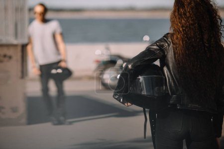 woman holding helmet and going to boyfriend with classic motorcycle