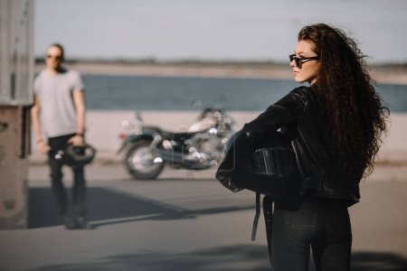 girl holding helmet and going to boyfriend with classical motorbike