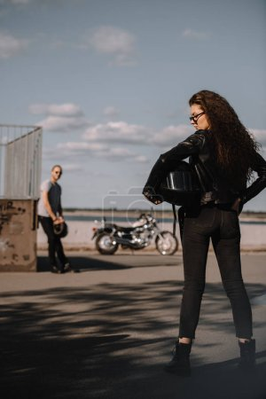 girl holding helmet and standing in front of boyfriend with motorbike