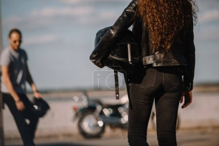 back view of girlfriend holding helmet and going to boyfriend with classical motorbike