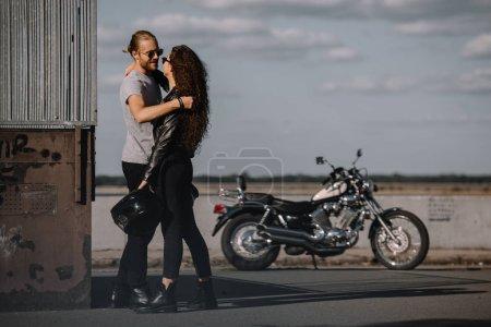 Photo pour Jeunes motards embrassant en ville avec moto classique sur fond - image libre de droit