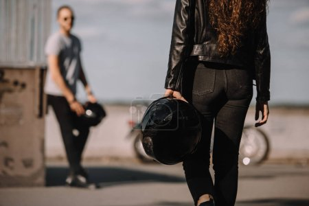 young couple of bikers with helmets and motorcycle
