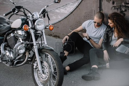 girlfriend and boyfriend sitting on asphalt with classical chopper motorcycle