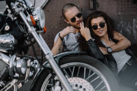 couple hugging and smoking cigarette on asphalt with chopper motorbike