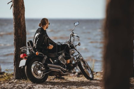 biker in leather jacket sitting on classical motorbike near the sea