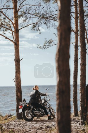biker in black leather jacket sitting on classic motorcycle near the sea in forest