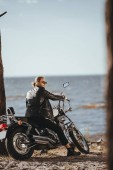 biker in black leather jacket sitting on chopper motorcycle near the sea