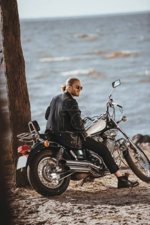 biker in black leather jacket sitting on classical chopper motorcycle near the sea