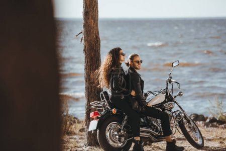 couple in black leather jackets sitting on classical chopper motorbike on seashore