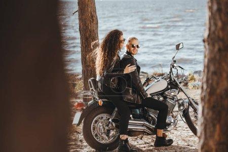 jeune couple de cyclistes dans les blousons en cuir noir assis sur la moto chopper au bord de mer