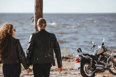 Photo for Rear view of couple holding hands and walking on seashore, classical motorbike standing near - Royalty Free Image