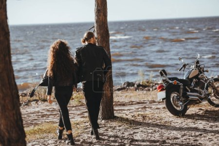 back view of couple holding hands and walking on seashore, cruiser motorcycle standing near