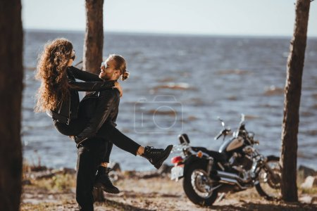 happy man holding his girlfriend on arms on seashore with classical motorcycle near