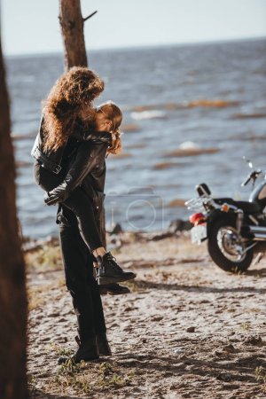 man holding his girlfriend on arms on seashore with cruiser bike near