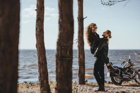 boyfriend holding his happy girlfriend on arms on seashore with motorcycle near