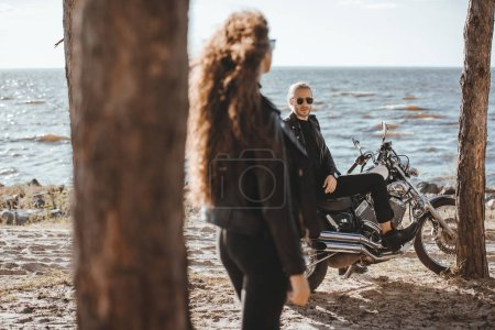 selective focus of woman looking at biker sitting on classical motorcycle on seashore