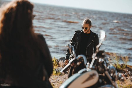 Photo for Selective focus of woman sitting on motorbike and looking at boyfriend walking on seashore - Royalty Free Image