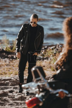 selective focus of girl sitting on motorbike and looking at boyfriend in black leather jacket