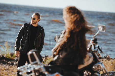selective focus of girlfriend sitting on vintage motorbike and looking at boyfriend in black leather jacket