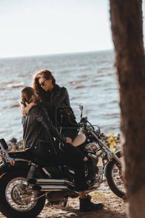young couple embracing on classical motorbike on seashore