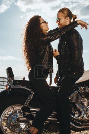 Couple in black leather jackets hugging on vintage motorbike