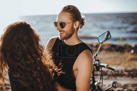 smiling couple spending time together near sea with motorbike