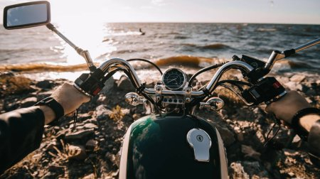 Camera point of view of biker sitting on classic motorbike on seashore