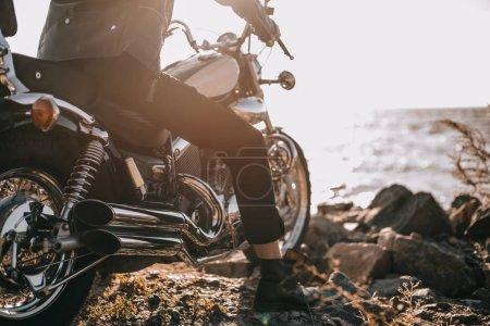 Photo pour Vue de la section basse du motard assis sur la moto classique à l'extérieur - image libre de droit
