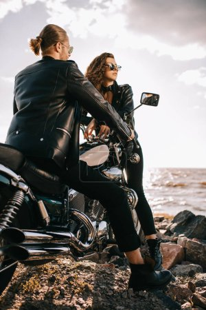 couple of bikers in black leather jackets with chopper motorcycle near sea