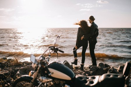 Photo for Selective focus of couple looking at sunset over sea and motorbike on foreground - Royalty Free Image