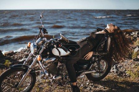 Photo pour Belle fille bouclée reposant sur la moto de croiseur classique - image libre de droit