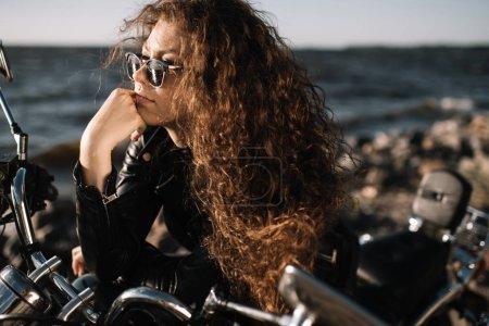 attractive curly female biker in sunglasses sitting on motorbike