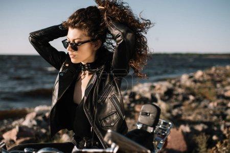 Foto de Hermosa chica rizada en gafas de sol sentado en la motocicleta - Imagen libre de derechos