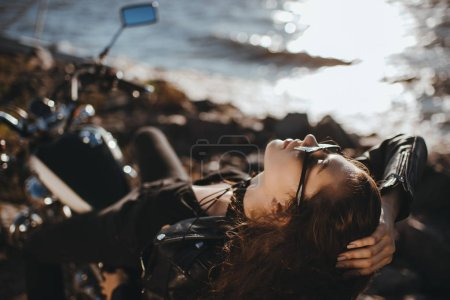 beautiful girl in sunglasses lying on classical motorcycle