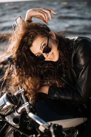 beautiful young woman smiling and sitting on classic motorbike