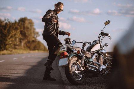 frustrated male biker kicking broken motorcycle on road