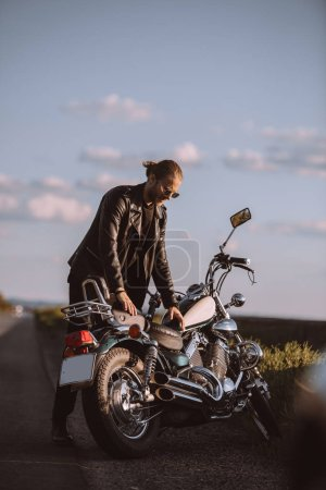 handsome male biker with classical motorcycle on road