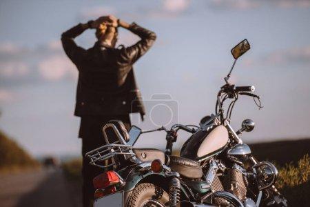 Photo pour Vue arrière du motard confondu avec moto cassée sur la route, mise au point sélective - image libre de droit