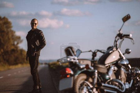 smiling man standing on road with classical motorcycle, selective focus