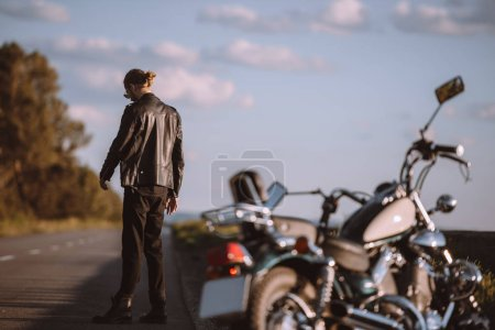 upset man with broken classic motorcycle on road, selective focus