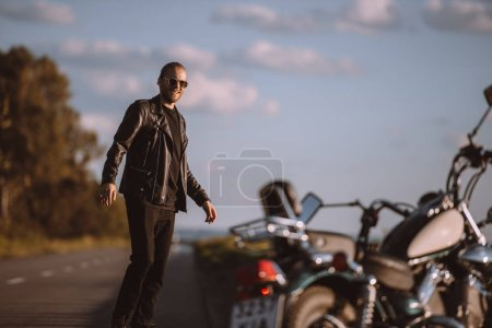 handsome man standing on road with classical motorbike, selective focus