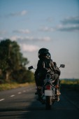 back view of bikers in helmets riding motorcycle on country road