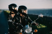 couple of bikers in helmets riding motorcycle