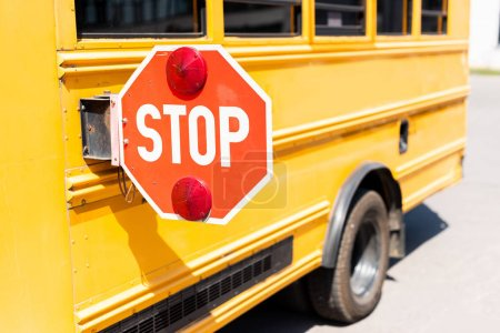 cropped shot of traditional school bus with stop road sign