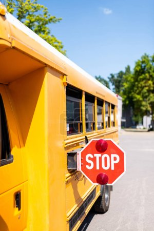 cropped shot of traditional school bus with stop sign