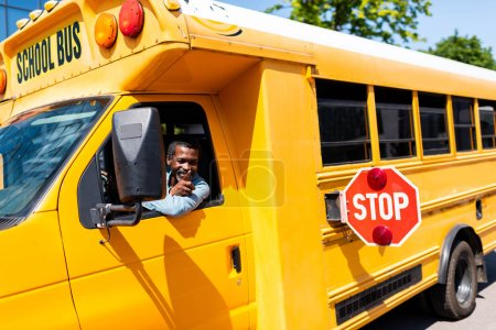 Photo for Smiling mature african american bus driver looking out window and gesturing - Royalty Free Image